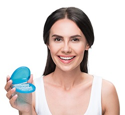 woman holding clear aligner in blue travel case