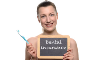 Woman with toothbrush and dental insurance sign